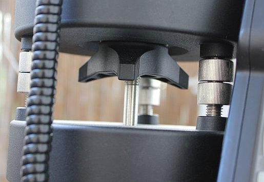 Trzy śruby poziomujące i duża śruba blokująca azymut