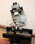 Very gently remove the webcam board from the bottom housing part and disconnect the power cable